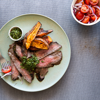 sliced steak with green chimichurri sauce and roasted sweet potatoes and a side tomato salad
