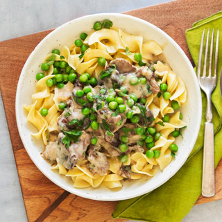 beef and mushroom stroganoff over butter noodles with fresh herbs, three drinks, a fork and spoon on a green napkin