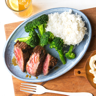 three thick slices of beef teriyaki with steamed broccoli and white rice on a blue plate on a light wooden cutting board