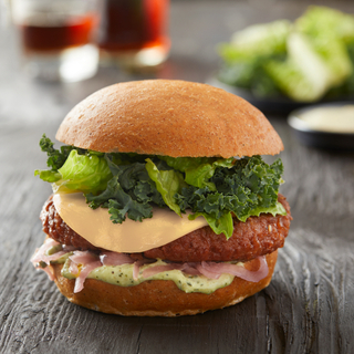 Side view of a beyond burger on a whole wheat hamburger bun with dairy-free melted cheese and raw kale on top.