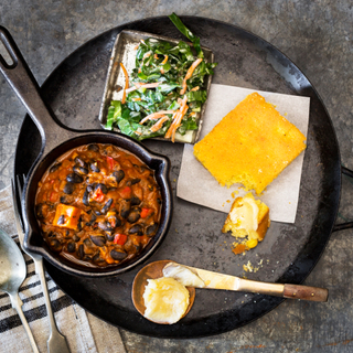 Black bean stew in a small cast iron skillet with slaw and cornbread and butter on the side in a larger round skillet on a dark concrete background with silverware.