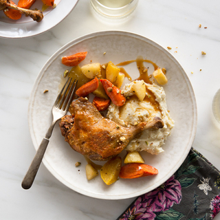 duck leg confit with mashed potatoes, roasted carrots and parsnips on a white dinner plate