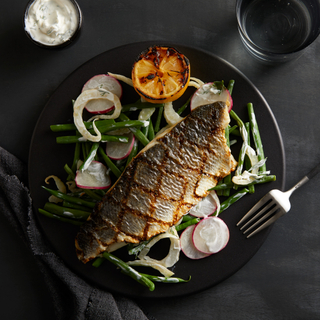 Half a grilled branzino sea bass on a bed of green beans, sliced radishes and onions with charred lemon on the side of a black round plate on a black background with a glass of water on the side.
