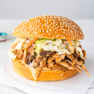 Sesame seed brioche bun with pulled barbecue pork inside and raw coleslaw on a white piece of parchment paper with a glass of clear drink in the background and a blue straw.