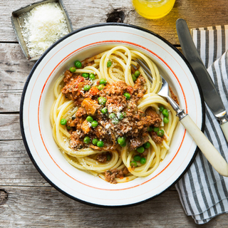 bucatini pasta with bolognese sauce and fresh peas on a wooden table with a blue striped napkin