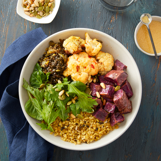 White bowl with grains, roasted cauliflower, lentils, roasted red beets on a blue wooden table with yellow salad dressing on the side and a bowl of pistachios and a blue napkin.