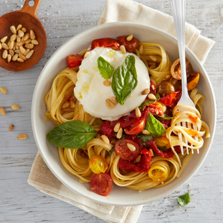 Fettuccine noodles with cherry tomatoes and a ball of burrata cheese in a white bowl on a white wooden background.