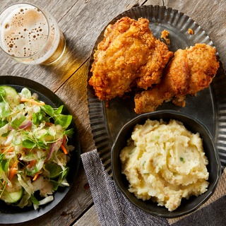Buttermilk fried chicken drumstick and thigh on a tin tray with mashed potatoes and a salad on the side with a glass of beer on a wooden table.