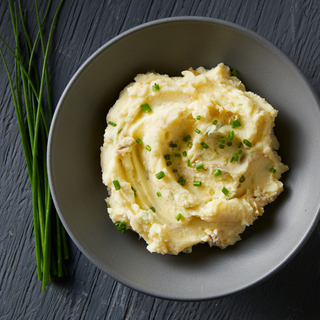 Buttermilk mashed potatoes garnished with sliced chives in a black bowl on a black table with whole fresh chives on the side.