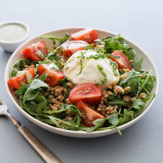 caprese salad with burrata, farro, arugula and tomatoes in a white bowl