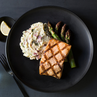 char-grilled salmon fillet with mashed potatoes and steamed broccoli on a black plate