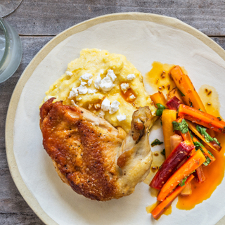 Roasted chicken thigh with skin on over feta polenta with cooked carrots on a white plate on a wooden table.