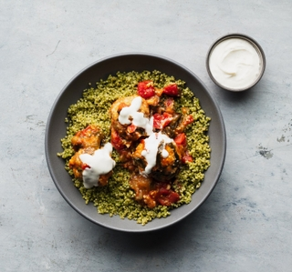 grey round bowl with cilantro quinoa and three ground chicken meatballs with tomatillo sauce and cumin yogurt on top