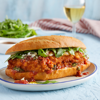 White dinner plate with a chicken parmesan sub on a long roll with tomato sauce, fresh herbs and a glass of white wine in the background.