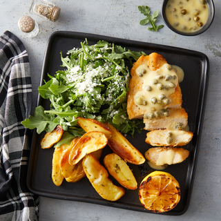 Chicken piccata breast with caper sauce next to fresh arugula salad with cheese and roasted sliced potatoes and a charred lemon half on a black square plate.
