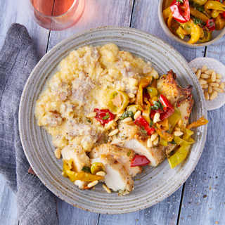 Polenta with sliced grilled chicken breast topped with marinated colored bell peppers on a ceramic plate on a wooden table with a glass of rose wine.