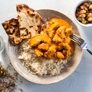 Chicken tikka masala on white basmati rice with crisp naan and a side of vegetables with a fork on a white background.