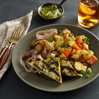 grilled chimichurri tofu with charred red onions and roasted root vegetables on a dark green dinner plate