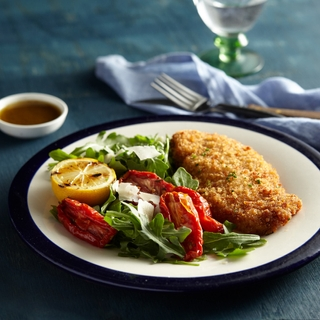 breaded chicken milanese with a salad of tomatoes, lettuce and lemon on a white dinner plate