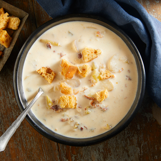 Creamy white clam chowder with crisp croutons on top and a spoon in the bowl with a blue napkin.