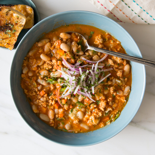 Creamy white bean and chicken chili with garnish in a teal bowl next to toasted bread on a white marble background.