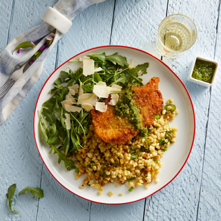 Crispy parmesan baked chicken over a bed of corn kernels with a salad of fresh arugula and shaved cheese on a white wooden table with a glass of wine.