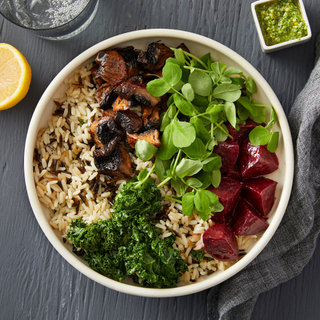 Round dinner plate with an earth bowl of rice, kale, watercress, steamed red beets, mushrooms and a green salad dressing on the side in a white square bowl.