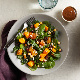 White dish filled with a green salad with chunks of butternut squash with a metal fork next to a glass of water and a dish of brown salad dressing.