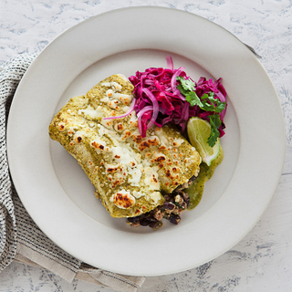 two farro enchiladas with red cabbage slaw and cheese on a white plate with a striped napkin on the side