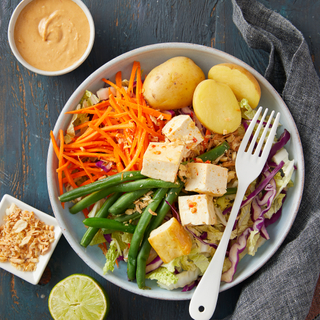 Gado Gado salad with boiled potatoes, cubed tofu, matchstick carrots and green beans with peanut dressing in a small dish on the side and a fork on top.