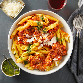 White bowl filled with garganelli pasta topped with sausage ragu, green dressing, shaved cheese with silverware on the side and a glass of red wine above.