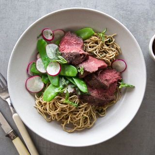 White dish with ginger garlic marinated flank steak sliced on top of wheat noodles with raw radish slaw on top, next to a fork and knife on a grey background.