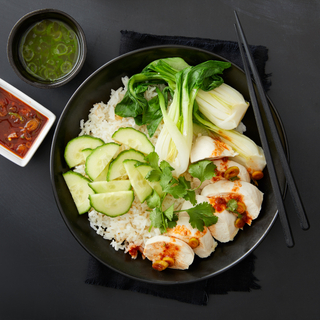 Ginger poached chicken breast on white rice with bok choy and sliced cucumbers in a black bowl with black chopsticks on a black napkin on a black table.