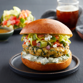 Side view of a small black plate with a Greek chicken burger on a bun with tzatziki and chopped Greek salad with another plate of salad in the background and a glass of beer.