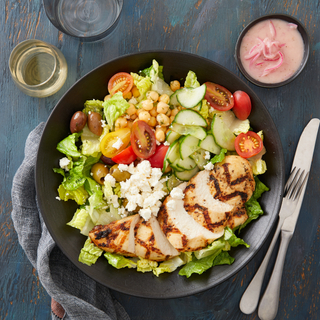 Greek chicken salad with greens, sliced tomatoes, cucumbers, sliced grilled chicken on a black plate with a side of vinaigrette in a black dish on the side with a knife and fork.