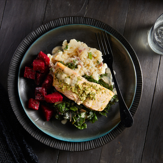 Black and blue layered dinner plates with gremolata roasted salmon, roasted chopped red beets, mashed potatoes and sauteed greens with a black fork.