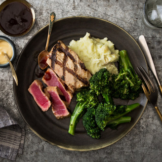 grilled sliced tuna steak with wasabi mashed potatoes and greens on a dark dinner plate on a concrete background