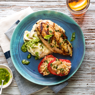 Grilled chicken breast with pesto and mashed potatoes with parmesan roasted tomato halves on a bright teal plate on a wooden background.