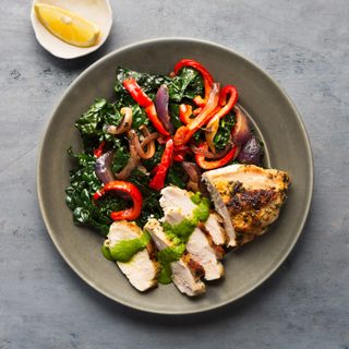 Sliced grilled chicken breast with roasted kale and bell peppers drizzled with green sauce on a black plate next to a white dish with a lemon slice.