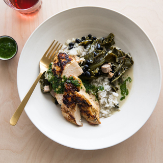 white bowl with chimmichurri chicken breast and coconut milk-braised collard greens with rice and beans
