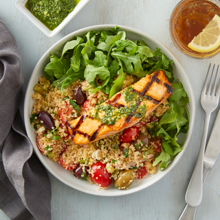 Grilled pesto salmon over quinoa with tomatoes and greens in a white diner bowl on a light grey background.