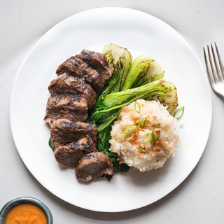 white round plate with sliced grilled red curry steak, sticky rice and grilled baby bok choy