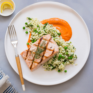 grilled salmon fillet over orzo pasta salad with fresh peas and romesco puree on a white dinner plate