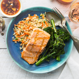 Grilled salmon with ponzu sauce on a bed of basmati rice salad and roasted broccolini with a side of soy dressing on a white wooden table.