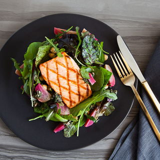 grilled salmon fillet on a salad of spinach, red beets and chickpeas on a black plate with silverware