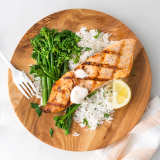 Wooden round plate with white rice, grilled salmon and cooked broccoli with a silver fork and a lemon wedge on the side.