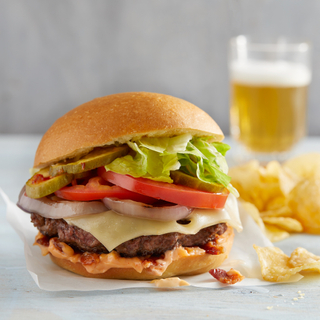 Side view of a burger on a bun with melted swiss cheese, sliced tomato, red onions, chopped lettuce next to potato chips and a glass of beer in the background.