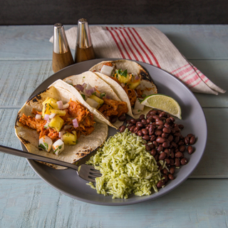 three honey chipotle chicken tacos with green rice and beans on a grey dinner plate