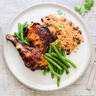 honey lime chicken thigh and leg on a plate with green beans and dirty rice and beans