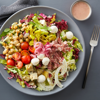 Italian chopped salad with mozzarella balls, sliced tomatoes, radicchio, chickpeas and green lettuce on a round plate with a side of vinaigrette dressing in a small dish.